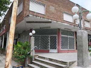 """Local vacío en la calle Tronador 4280. En su puerta figura: """"Federación Argentina de Lavanderías Tintorerías Transportes y Afines""""."""