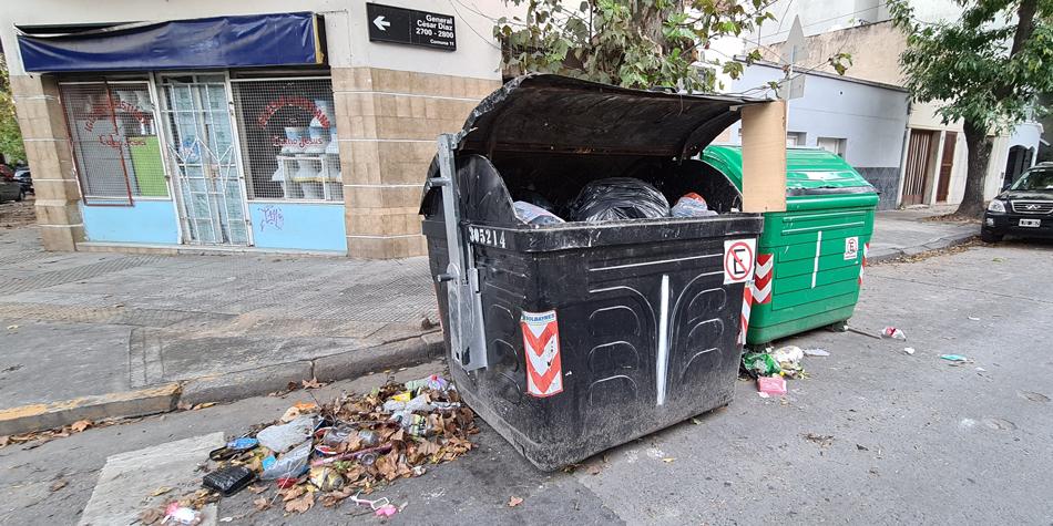 Esquina de Gral. Cesar Díaz y Terrada en la Comuna 11 el 11/04/2021. Ambos contenedores rodeados de basura están en infracción sobre la ochava bloqueando la visión a los automovilistas y sobre la parada del colectivo de la línea 110.