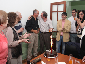Mientras los presentes aplauden, Marcelo Ruiz abraza a Adrián Hilarza luego de encender la velita de la torta de los 10 años de AIPH.